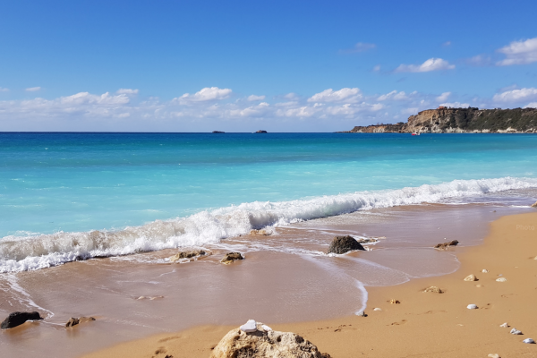 A turquoise blue sea and golden sand at Avithos Beach in Kefalonia, Greece